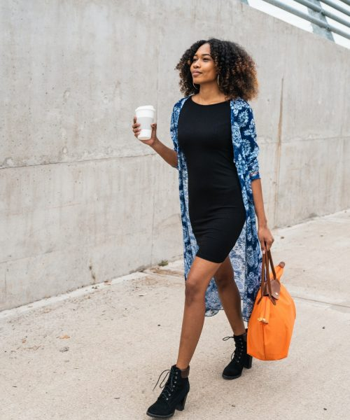 Afro american woman walking with coffee.